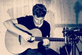 Tom Ryder playing acoustic guitar